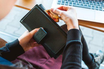 Imagem de uma pessoa segurando seu cartão de crédito
