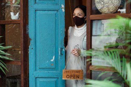 Mulher vestindo uma máscara na porta do seu comércio
