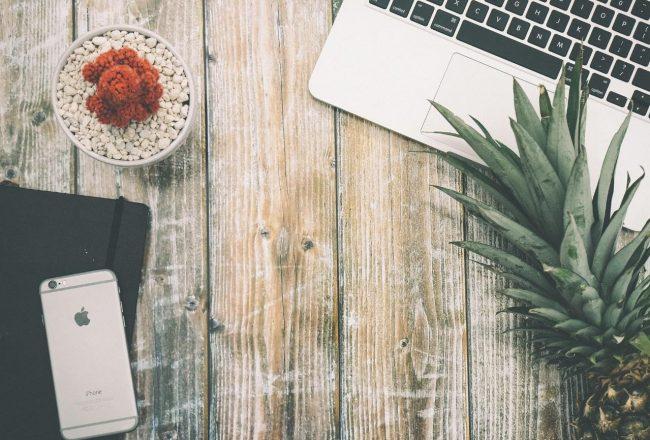 Mesa de madeira mostrando apenas o teclado do notebook, com a coroa do abacaxi sobre ele, com um caderninho de anotações na outra ponta da imagem, com um celular em cima. Imagem usada para representar quais são os benefícios de usar o Abacashi