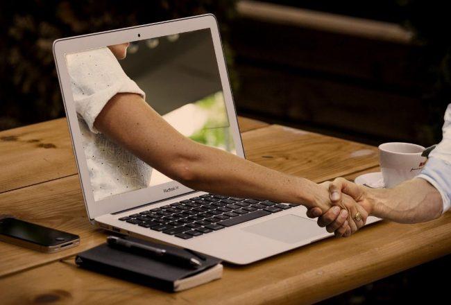 Vaquinhas online que deram certo: braço saindo de um notebook e apertando a mão de uma pessoa que estava utilizando o notebook, sobre uma mesa de madeira com celular, caderninho de anotações, caneta e xícara de café.