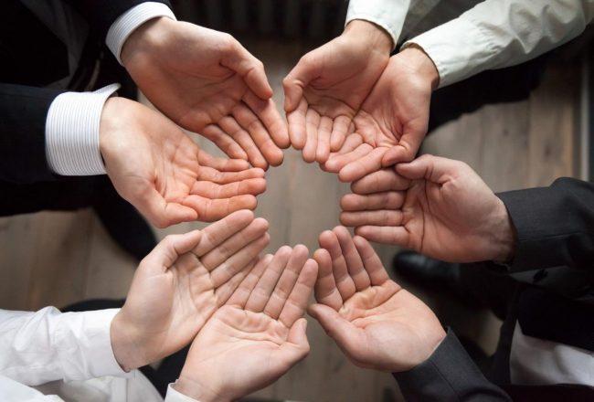 Várias mãos de empresários unidas em círculo: tipos de crowdfunding