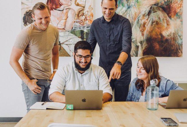 Colegas de trabalho reunidos em volta do computador: financiamento coletivo para empresas